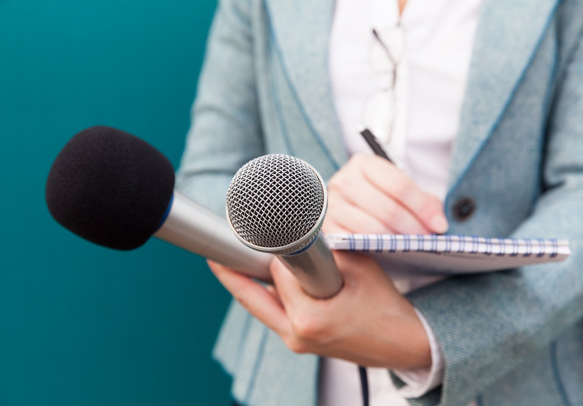Female reporter taking notes at press conference. Photo: iStock
