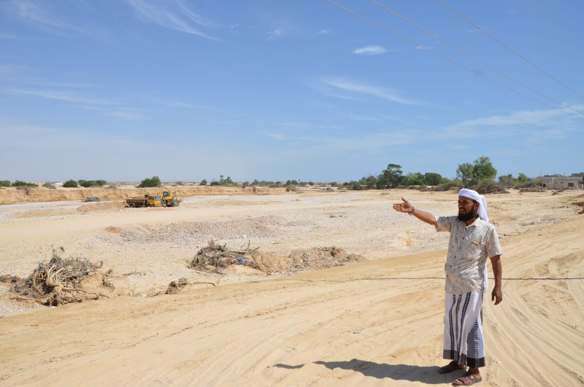 Nabeel, a math teacher in the southeastern Yemeni city of Ghaida, points to a new waterbed formed by flash floods during a cyclone in mid-October. Photo: Saeed Al-Batati