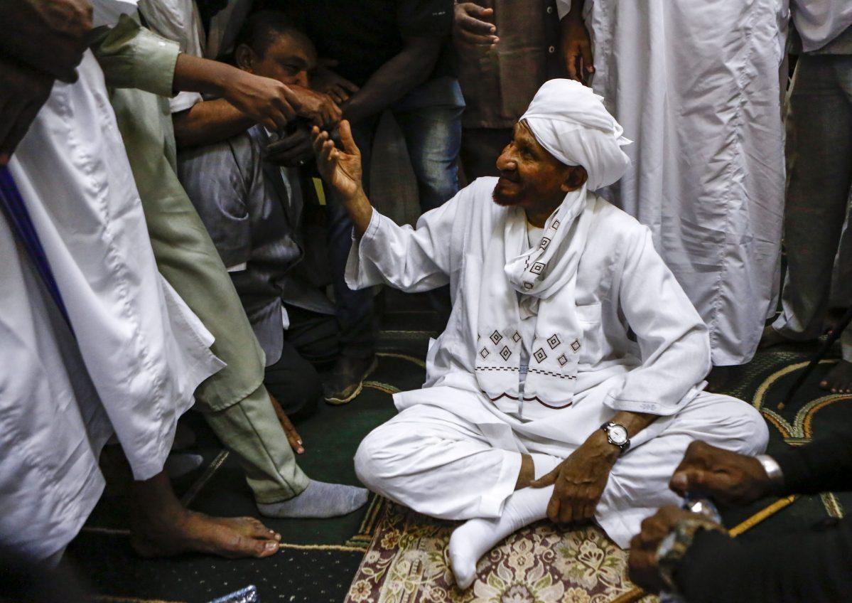 صادق المهدي، رئيس الوزراء السوداني السابق والقائد المعارض يحاوطه مساندون في جامع في مدينة أم درمان في 19 ديسمبر/كانون الأول 2018. صورة: ASHRAF SHAZLY / AFP