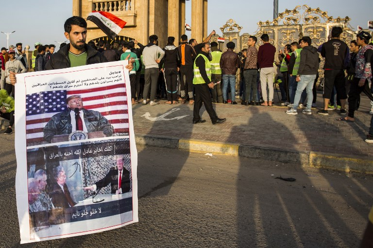 """An Iraqi protester holds up a sign showing US President Donald Trump with a caption reading in Arabic """"Trump replies to journlaists, 'I didn't meet with Iraqi officials because they rob their country and I don't respect country-robbers. Photo: AFP"""