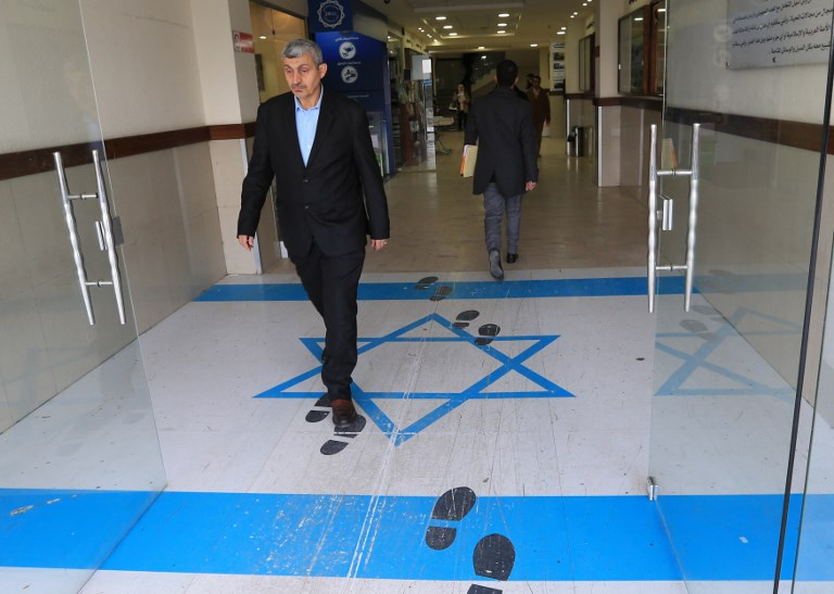 A man leaving a trade union complex in the Jordanian capital Amman steps on an image of an Israeli flag on Sunday. Photo: AFP
