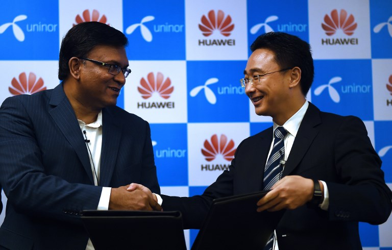 Chief operating officer of Uninor Tanveer Mohammad shakes hands with Huawei vice-president Baker Zhou  in 2015 after signing a deal to modernize India's entire telecom network. Photo: AFP