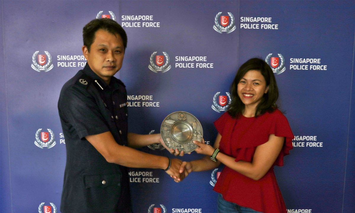 Deputy Assistant Commissioner of Police Goh Wee Khern presented the Public-Spiritedness Award to the passenger. Photo: Singapore police
