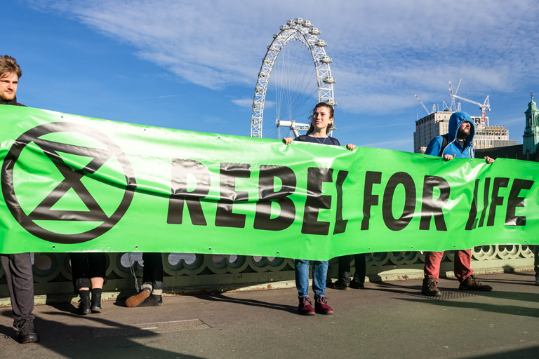 Extinction Rebellion activists hold a banner in the UK. They want people around the world to take more radical action against climate change. Photo: @ Thomas Katan.