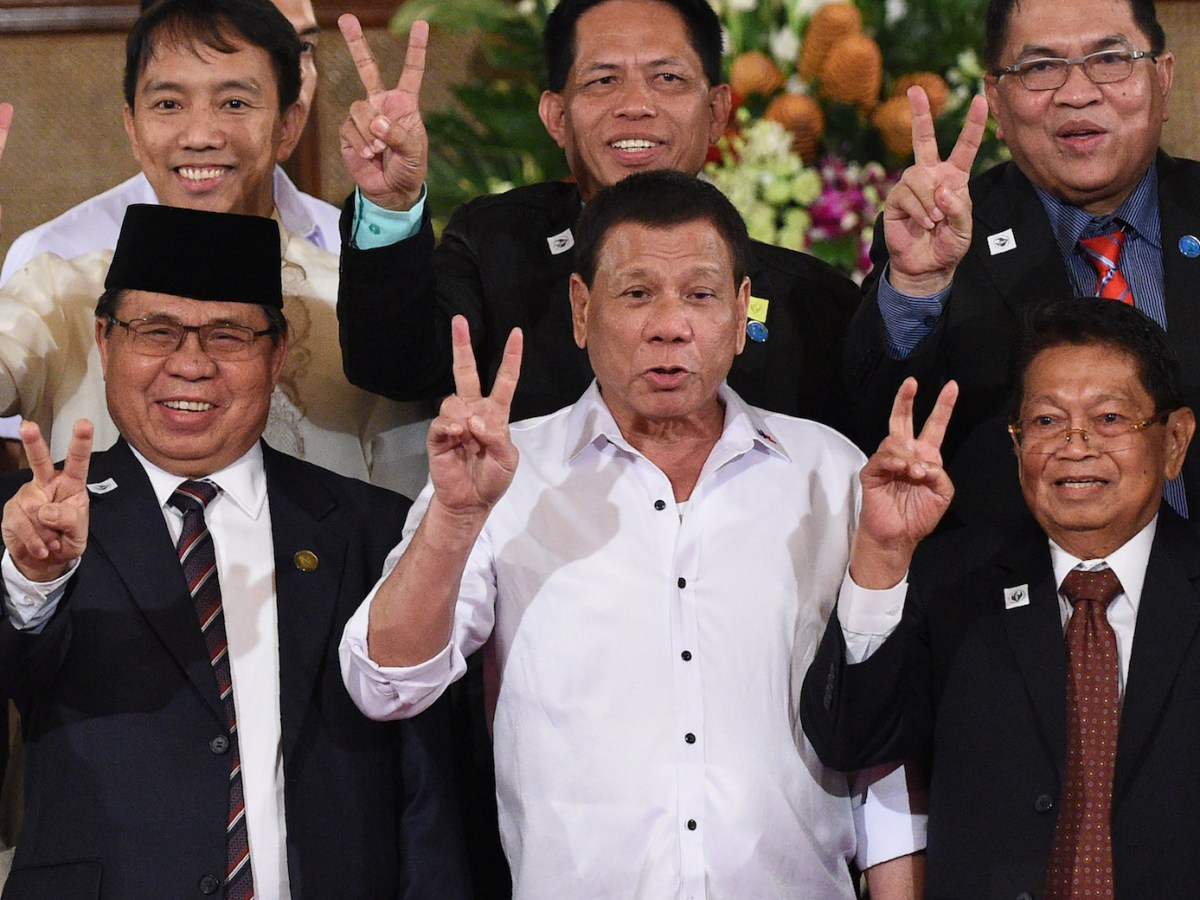 Al-Hajj Murad, Moro Islamic Liberation Front (MILF) chairman, Philippine President Rodrigo Duterte and Ghazali Jaafar, vice chairman of MILF, gesture with the peace sign during a ceremony for Bangsamoro Organic Law draft being submitted to the president at the Malacanang Palace. Manila, July 17, 2017. Photo: AFP/Ted Aljibe