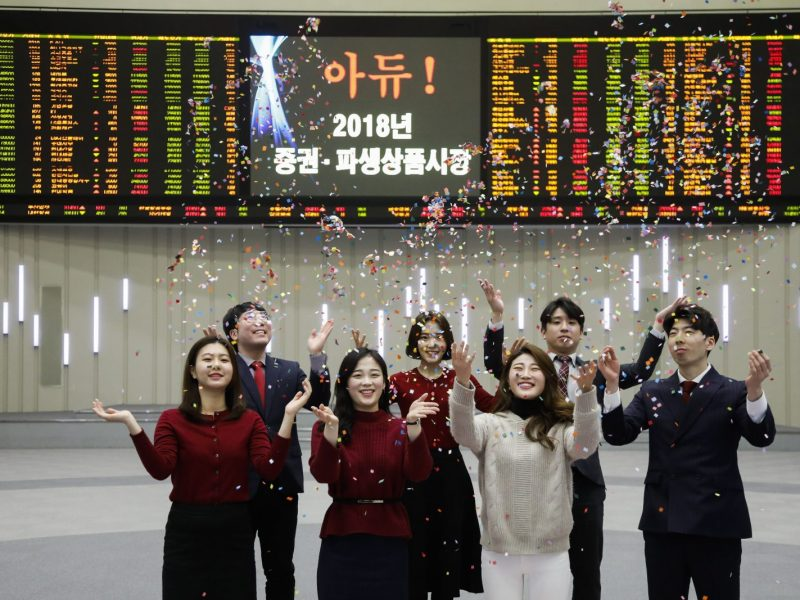 Staff members of the Korea Exchange applaud as they throw confetti for the media during the year's market closing ceremony at the Korea Exchange in Seoul, South Korea, on December 28, 2018. Photo: AFP/Seung-il Ryu/NurPhoto