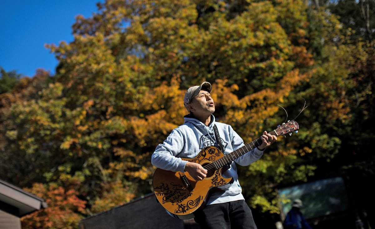 Musician Kyochi Watanabe plays his guitar at the entrance of Aokigahara Forest, known as Suicide Forest, in Narusawa village, Yamanashi prefecture. Photo:   Behrouz Mehri / AFP