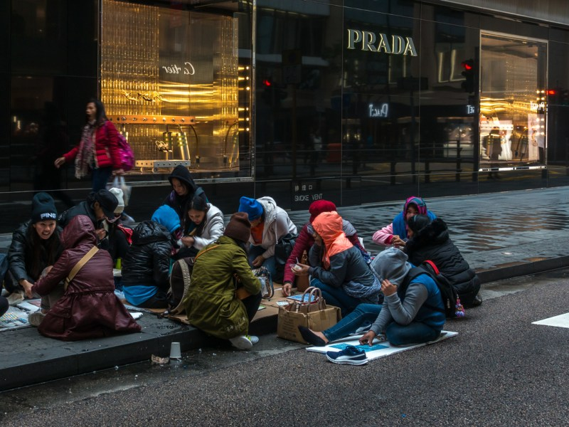 Female workers from Indonesia and the Philippines gathering on Sunday on the streets of Hong Kong Central near luxury shops. Hong Kong, January 2018. Photo: iStock