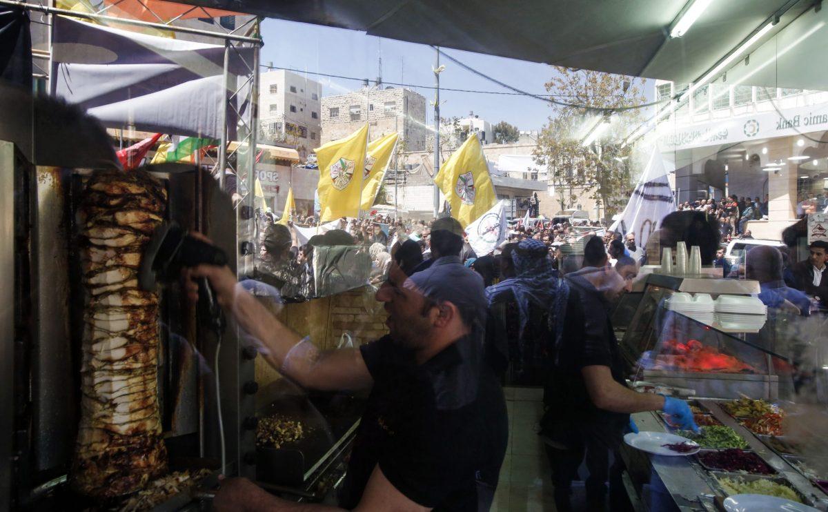 صورة من داخل مطعم شاورما في مدينة الخليل بالضفة الغربية في 17 أبريل/نيسان 2017، تظهر في خلفيتها مظاهرات دعم للمعتقلين الفلسطينيين. صورة: HAZEM BADER / AFP