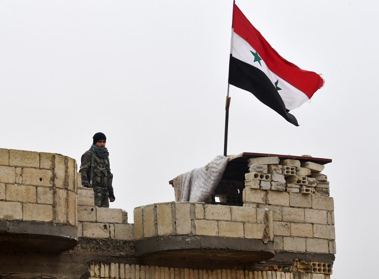 A Syrian army soldier stands guard outside Manbij, Aleppo Province, Syria. Photo: AFP