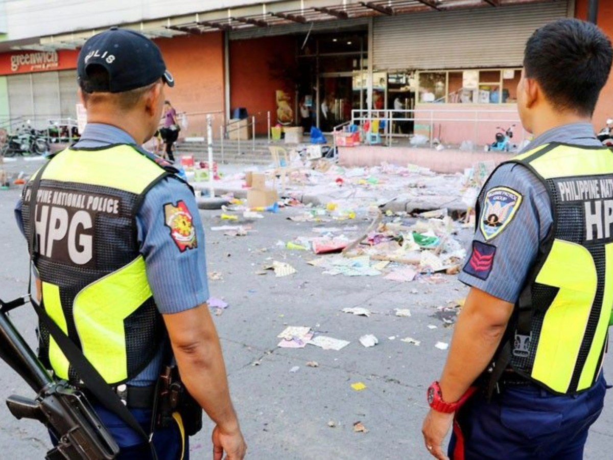 Philippine police stand in front of the aftermath of a terrorist bomb attack at a shopping center in Cotabato City, December 31, 2018. Photo: Twitter