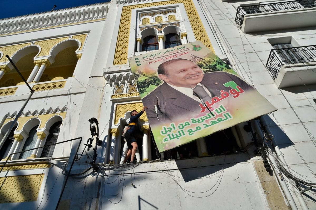 متظاهرون جزائريون يحطمون لافتة دعائية كبيرة تحمل صورة الرئيس عبد العزيز بوتفليقة في 22 فبراير 2019 في العاصمة الجزائر. صورة: RYAD KRAMDI / AFP