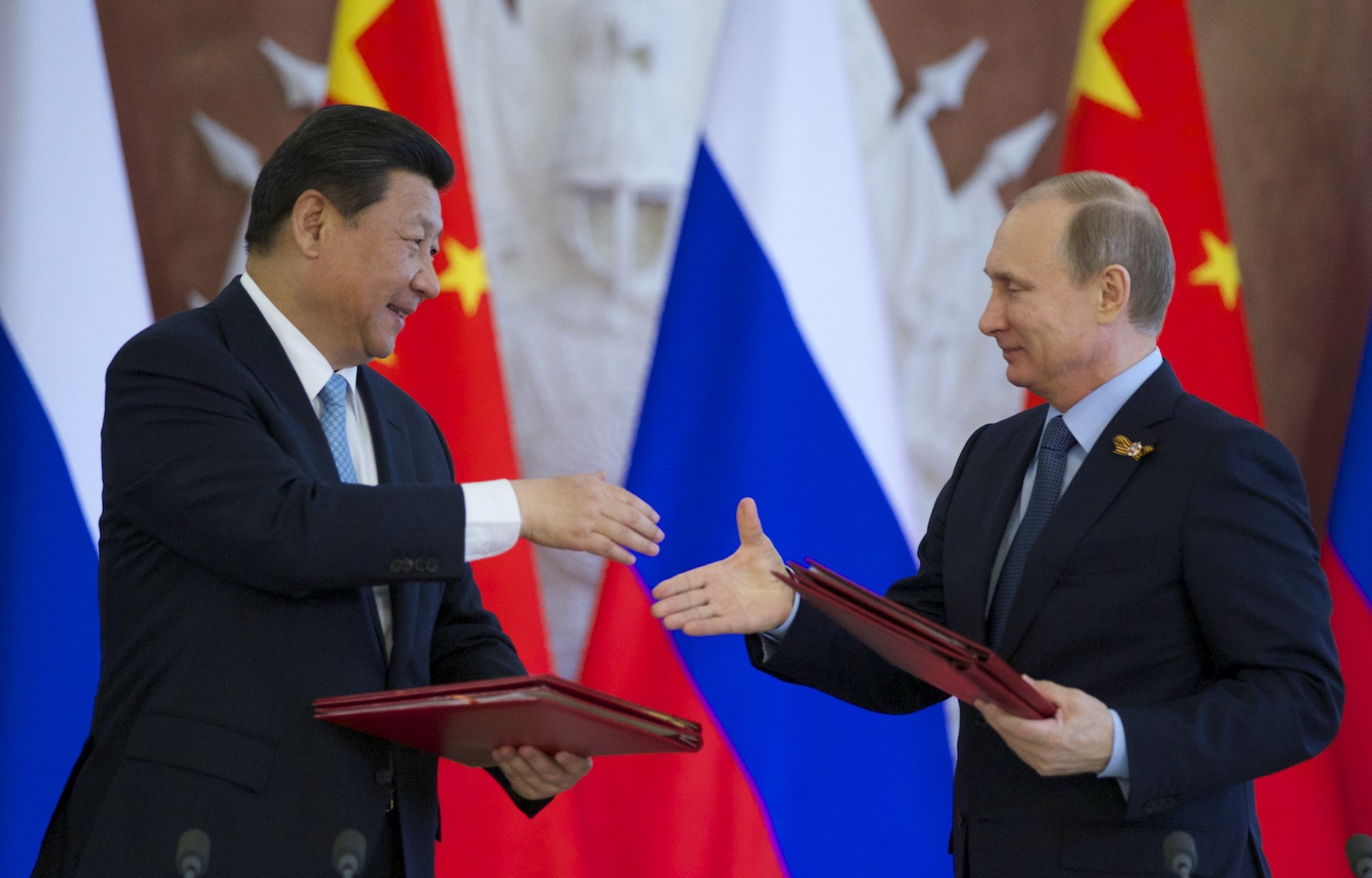 Russian President Vladimir Putin, right, and Chinese President Xi Jinping exchange documents at the signing ceremony in the Kremlin in Moscow in a file photo. Image: Pool / Agencies