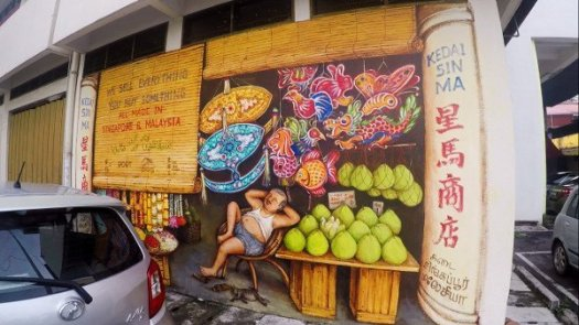 Things To Do In Ipoh - Mural Art of a Provision Store filled with fruits, lanterns, and goods with the store owner