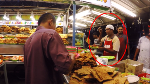 Famous Stall with Guy Who Sings and Dance (in red circle) as he prepares the food