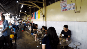 Long row of tables and chairs for customers to enjoy the Assam Laksa