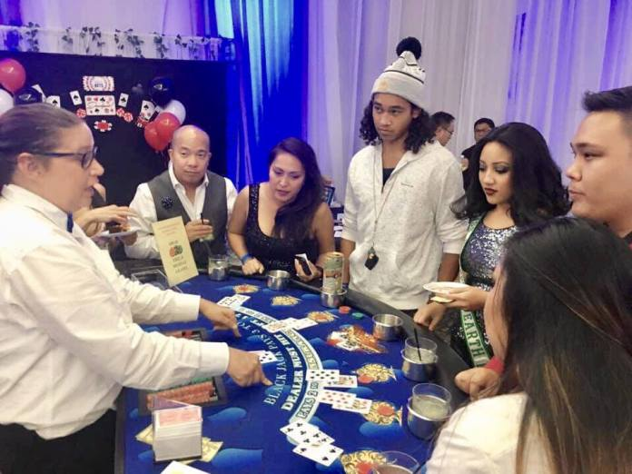 The guests getting free lessons on how to play with their paper money.