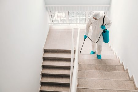 Worker in sterile uniform, with gloves and facial mask sterilizing stairs in school.