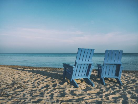 two blue chairs on the beach