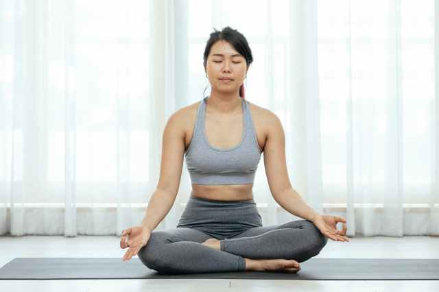 a woman meditating while sitting on a yoga mat