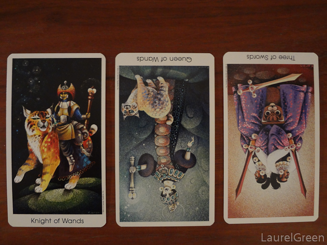 a three card tarot spread with the knight of wands, the queen of wands reversed and the three of swords reversed