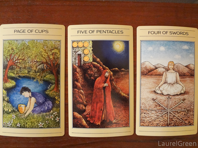 a three card tarot spread with the page of cups, the five of pentacles and the four of swords