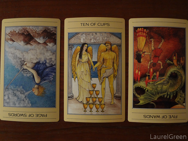 a three card tarot spread with the page of swords reversed, the ten of cups and the five of wands reversed