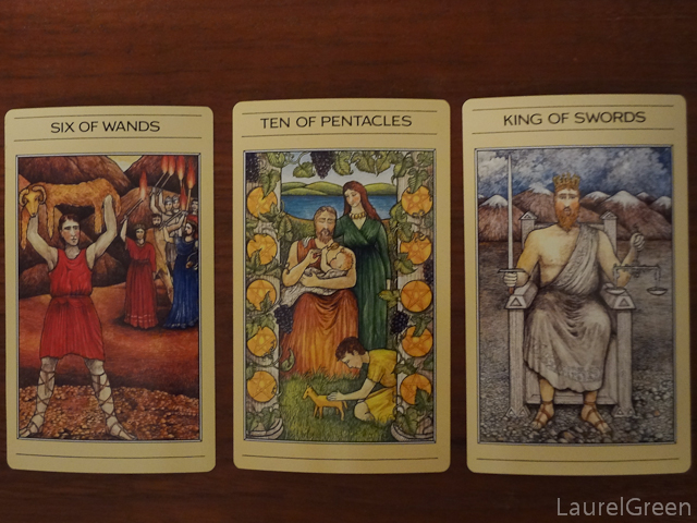 a three card tarot spread with the six of wands, the ten of pentacles and the king of swords