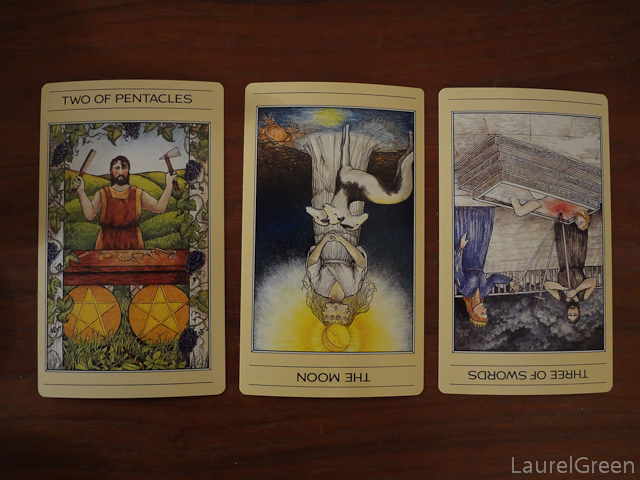 a photo of a three card tarot spread with the two of pentacles, the moon reversed and the three of swords reversed