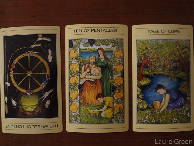 a three card tarot spread with the wheel of fortune reversed, the ten of pentacles and the page of cups