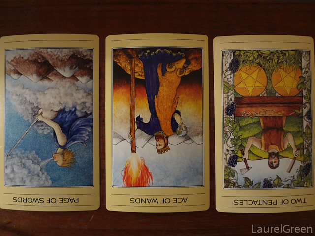 a three card tarot spread with the page of swords reversed, the ace of wands reversed and the two of pentacles reversed