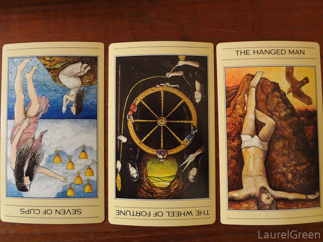 a three card tarot spread with the seven of cups reversed, the wheel of fortune reversed and the hanged man