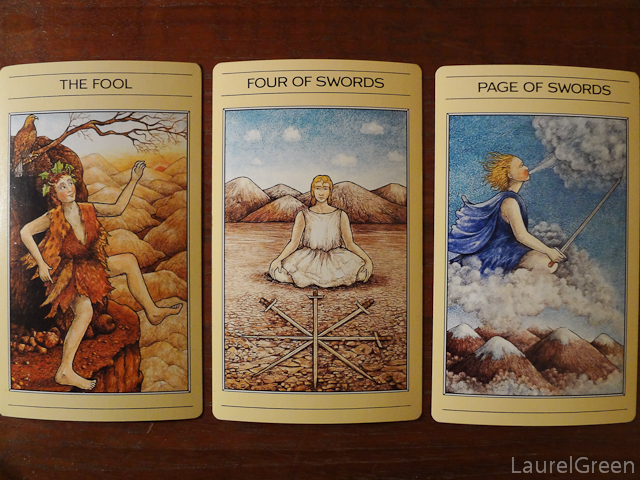 a three card tarot spread with the fool, the four of swords and the page of swords