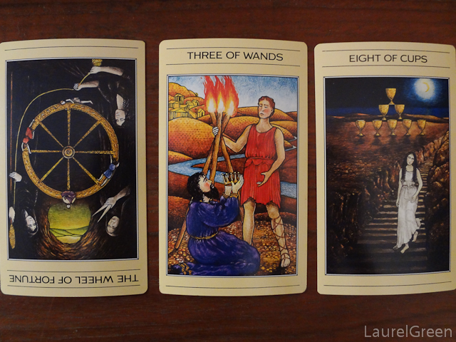 a three card tarot spread with the wheel of fortune reversed, the three of wands and the eight of cups