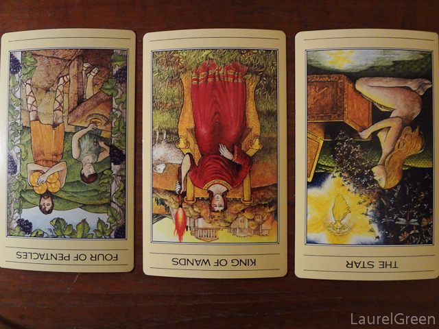 a three card tarot spread with the four of pentacles reversed, the king of wands reversed and the star reversed