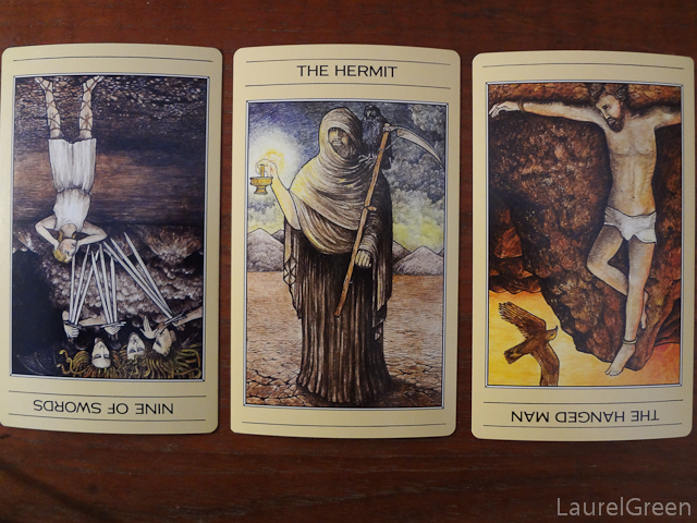 a three card tarot spread with the nine of swords reversed, the hermit and the hanged man reversed