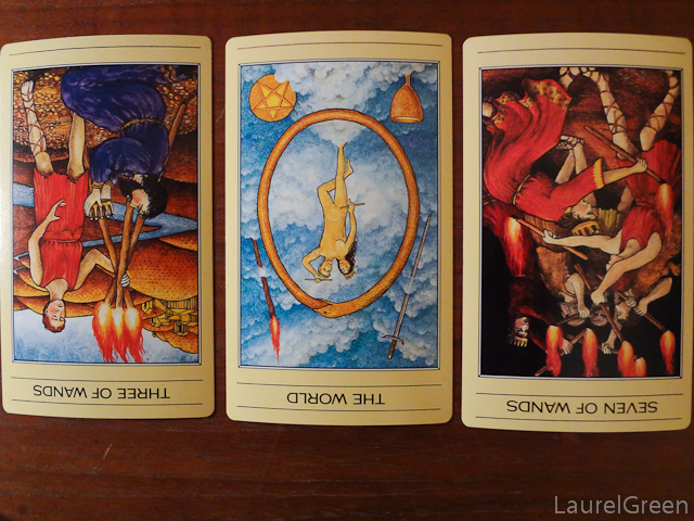 a three card tarot spread with the three of wands reversed, the world reversed and the seven of wands reversed