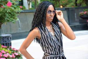 Young african lady in sunglasses and black striped dress looking boldly into the camera.