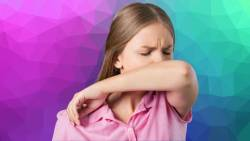 Lady coughing into a bent elbow - reduces the spread of Covid-19