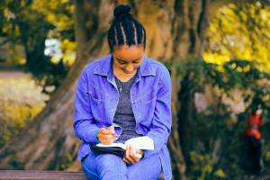 Haemoglobin C disease - african lady in blue deim coat and jacket with cornrows reading a book in a park.