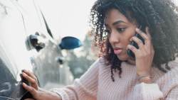 Young lady of African background talking on the phone and looking at damage to her car