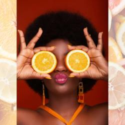 Lady with a frizzy afro in hot pink lipstick holding up 2 orange slices over her eyes