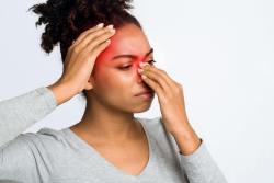 Loss of taste and smell, headaches are long covid symptoms - lady of african origin holding her nose and head in pain.