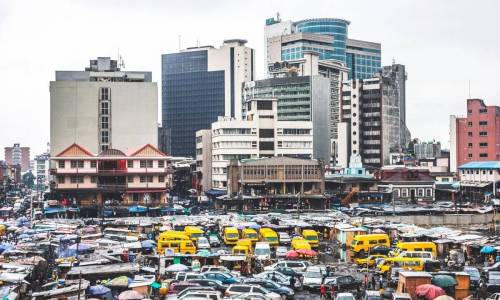 Picture of Nigerian city with distinctive bright yellow public transport buses in foregraound - for contraceptive use in Nigeria