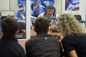 Expedition 37/38 NASA Engineer Michael Hopkins is seen speaking to his family after having his Russian Sokol suit pressure checked ahead of his launch onboard a Soyuz TMA-10M spacecraft to the International Space Station, on Wednesday, Sept. 25, 2013, in Baikonur, Kazakhstan. Launch of the Soyuz rocket will send the Expedition 37/38 crewmates on a five-month mission aboard the International Space Station. Photo Credit: (NASA/Carla Cioffi)