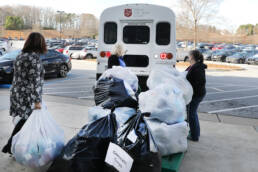 Photo of Primerica employees loading bags of blankets onto truck