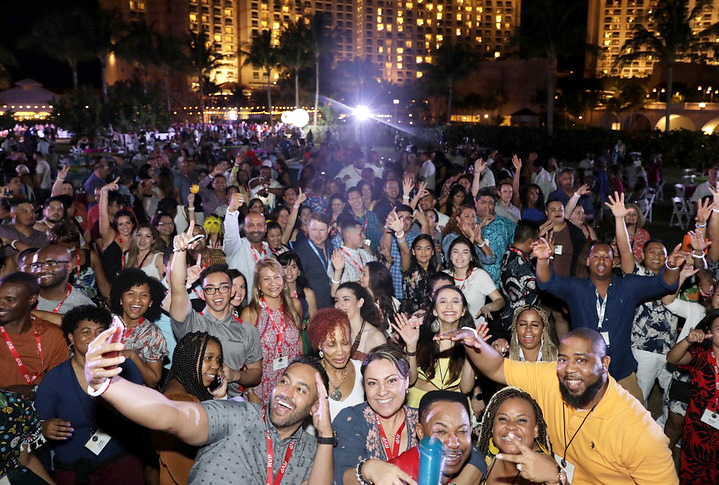 Large group of happy people gathered outdoors at night
