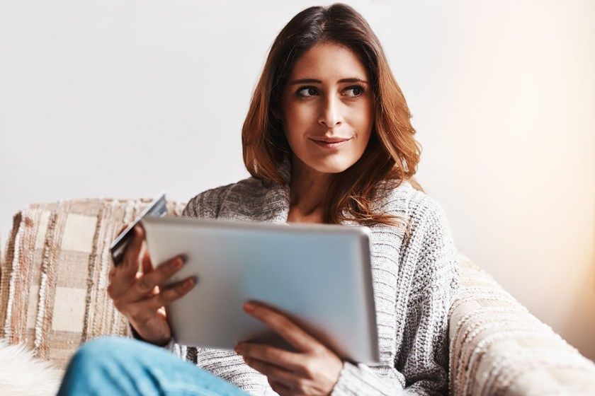 Shot of an attractive young woman using a digital tablet and credit card on the sofa at home