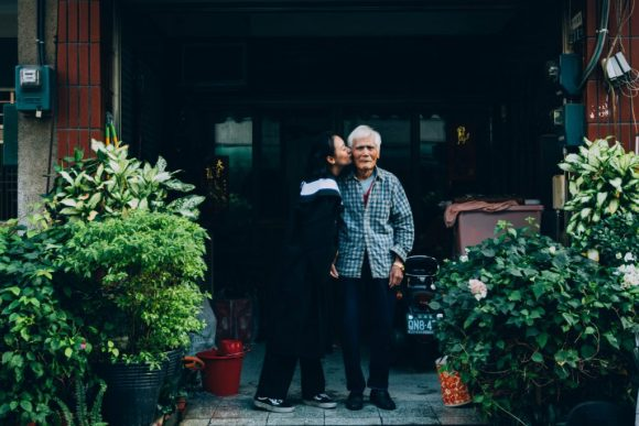 """Grandpa"" a photo of a woman kissing an old man's cheek outside an apartment building or storefront in a busy urban environment. He smiles and you can tell she loves him.  Photo by Treddy Chen on Unsplash"