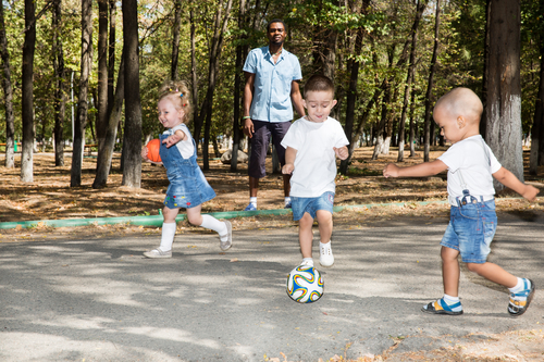 Group of happy children playing with soccer ball in park on nature at summer. Use it for baby and sport concept
